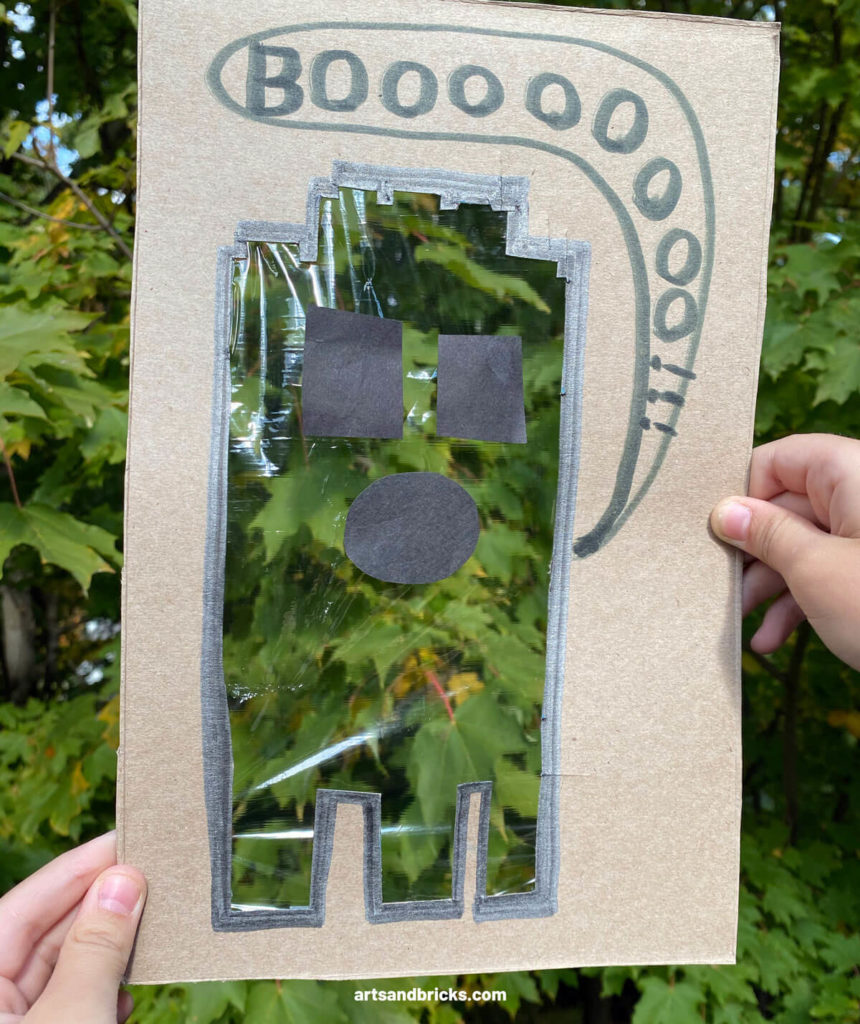 Explore your surroundings -- like  leaves in trees -- with this Ghost Peek-A-Boo Cardboard Craft! Use cardboard (we used a cereal box panel) to create a ghost. Ours is a LEGO brick ghost!!! Add plastic wrap over the body and tape on a spooky face. Don't forget to add a BOO! Next is the fun part, start framing textures and colors - both indoors and outdoors. Don't forget to take pictures! Have fun! #lego #craft #google #cardboard #forkids #easy #recycled #naturecrafts